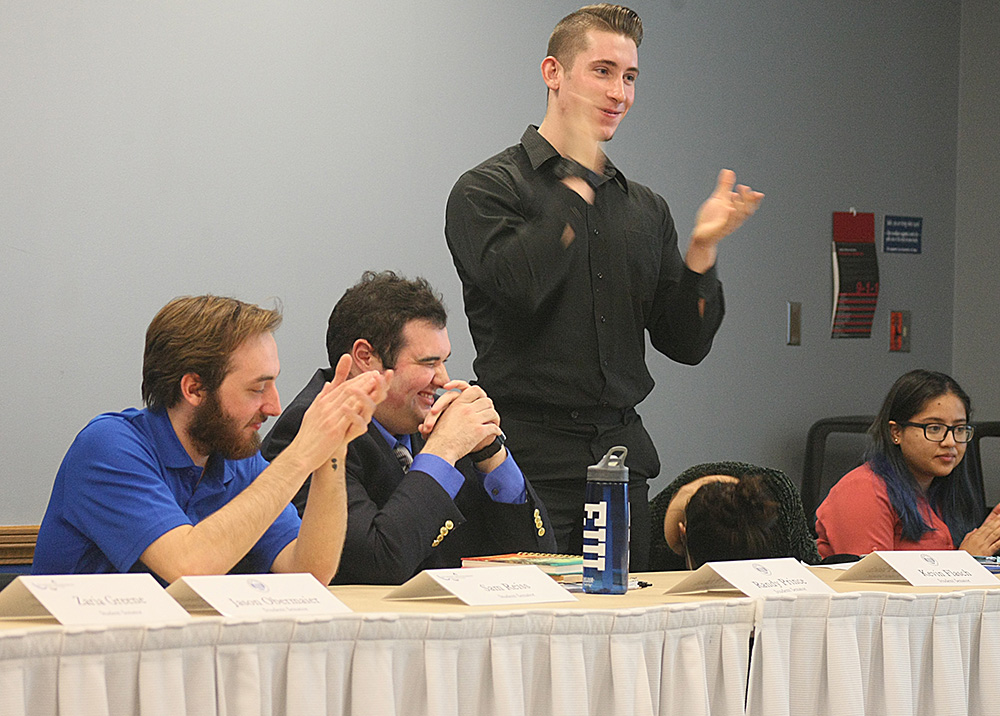 Kevin Flasch (standing), a student senator and senior business management major, gives a standing ovation to fellow senator Randy Prince (sitting to the left of Flasch), who said his goodbye to the Student Senate because he is graduating this semester.