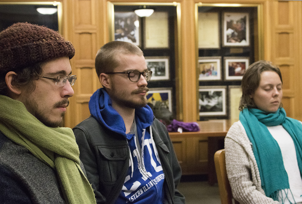 Alex Hill a graduate student and buissnes administration major, John Hader a senior kinisiology major and Michelle Meyeraholtz a senior a general studies major meditate during a guided meditation at Booth Library Sunday night.