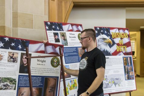 Rodney Rote Jr., a senior music performance major, sets up the exhibit