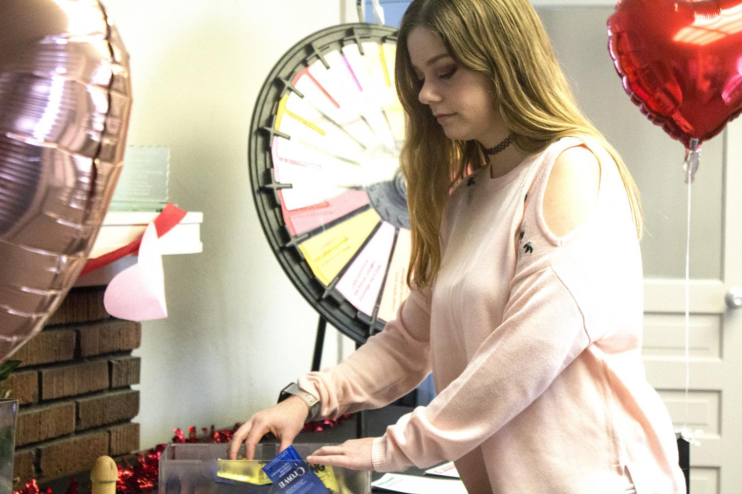 Emma Welton, a graduate assistant in communication studies, organizes free condoms provided by the HERC at the Spreading the Love and Wellness event in the Booth House on Thursday afternoon.