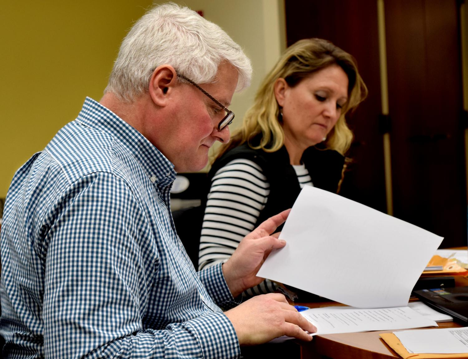 CAA vice chair Richard Wilkinson, a family and consumer sciences professor, sits with CAA chair Stacey Ruholl, a kinesiology and sports studies professor. They are looking through family and consumer sciences course proposals, all of which were passed unanimously at the Council on Academic Affairs' meeting Thursday.
