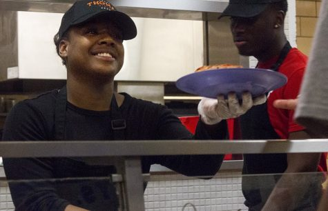 Daja'Nay Brown, a senior psychology major and a student worker at the Thomas Dining Center, hands a student his pizza Monday night during Late Night Pizza. Brown said though she is ready to graduate, it will be bittersweet.