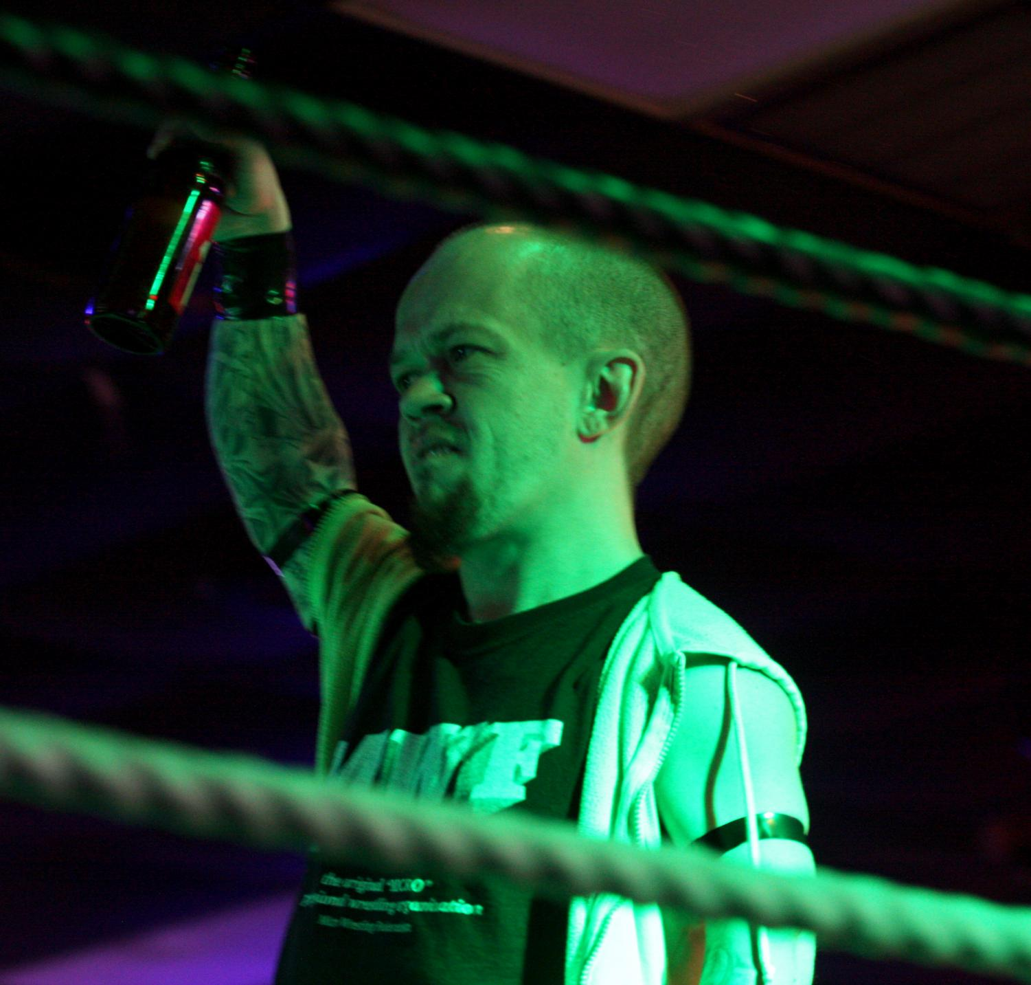 "JJ Bullock | The Daily Eastern ""The Enigma"" of the Micro Wrestling Federation holds a beer up for the crowd at the Panther Paw."