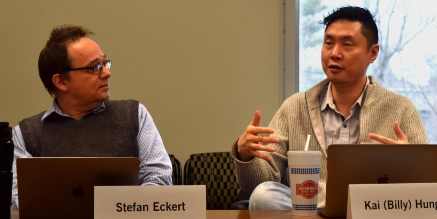 Music theory professor Stefan Eckert and biological sciences professor Billy Hung talk during a Faculty Senate meeting Tuesday in Booth Library.