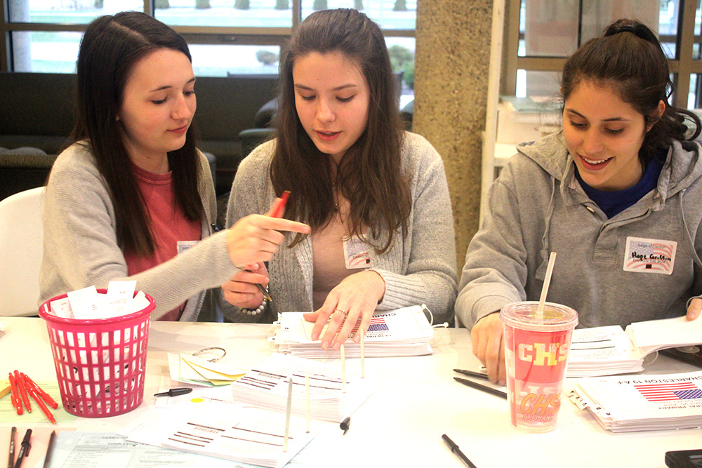 High School students Ashtyn Willheim, Ana Lawless and Hope Griffin organize election ballots at The Newman Catholic Center voting poll booth Tuesday evening. They were nominated to work as election judges by their teacher.