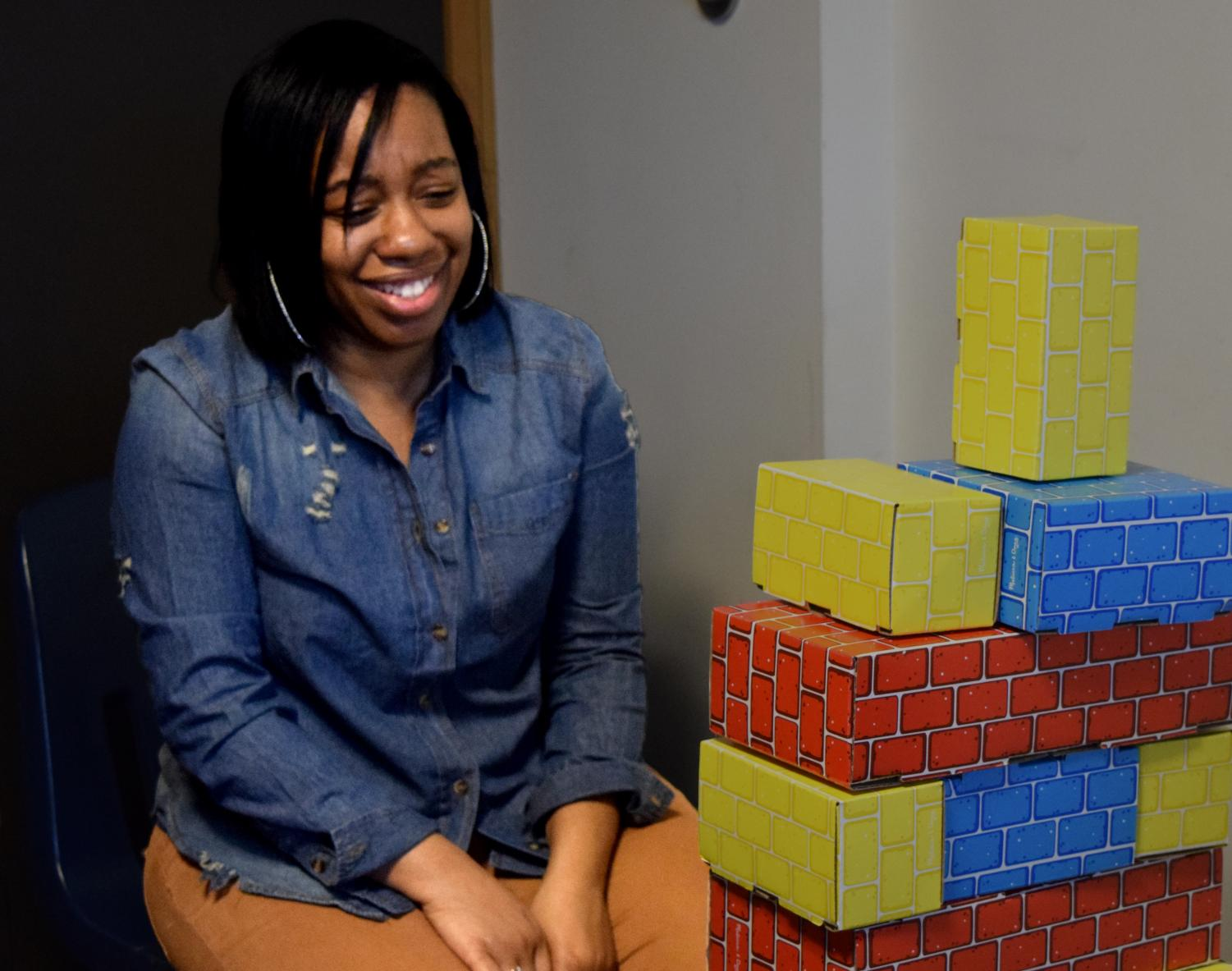 """LeLonna Goodson, a communication studies graduate student, is pictured at Tunnel of Opression Tuesday night in Thomas Hall. She built a tower with the """"restrictions"""" given to her on a card, to showcase the importance of noticing a person's strength versus their disability."""
