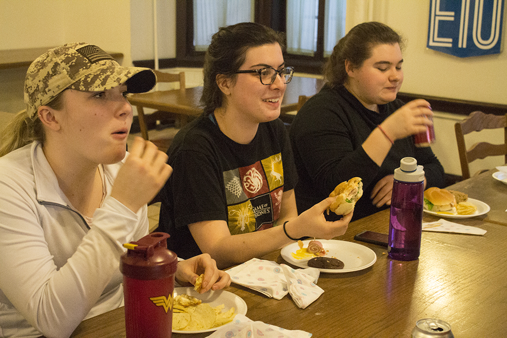 """Students, Kelsey Knopp, a sophomore special education major, Caroline Egan, a junior english major and Kayley LaGrou, a junior middle level education major dine on food during """"The Hunger Banquet"""" inside of Permberton Hall on Wednesday evening."""
