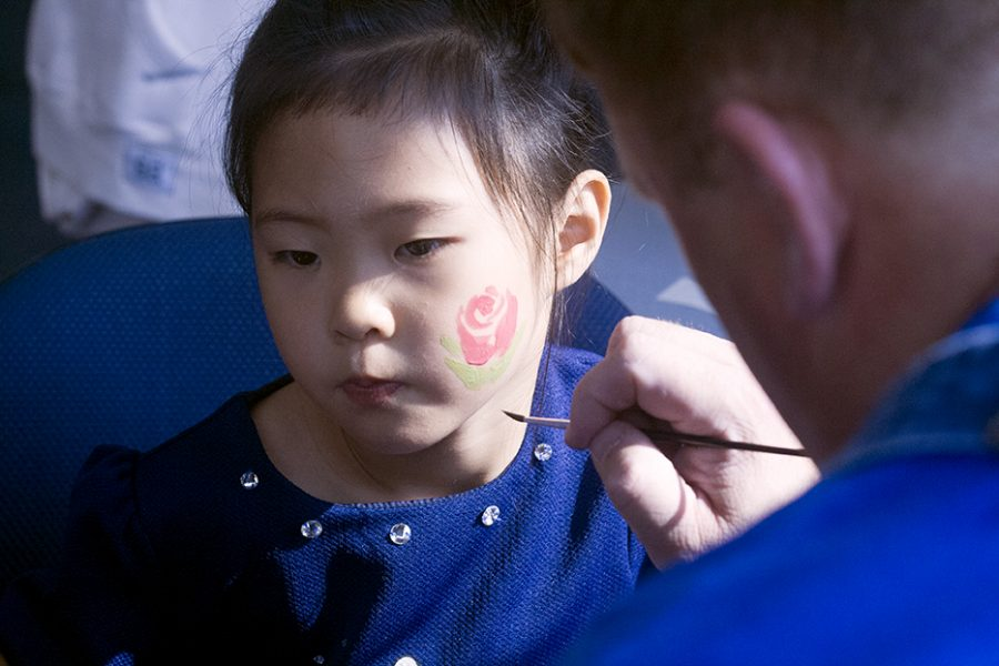 Mary Ellen Greenburg | The Daily Eastern News Christina Wang gets a flower painted on her cheek Saturday in the walkway lounge at the Martin Luther King Junior University Union. Christina is the daughter of the Chinese professor here at Eastern illinois University. This is the first semester that Eastern has offered Chinese.