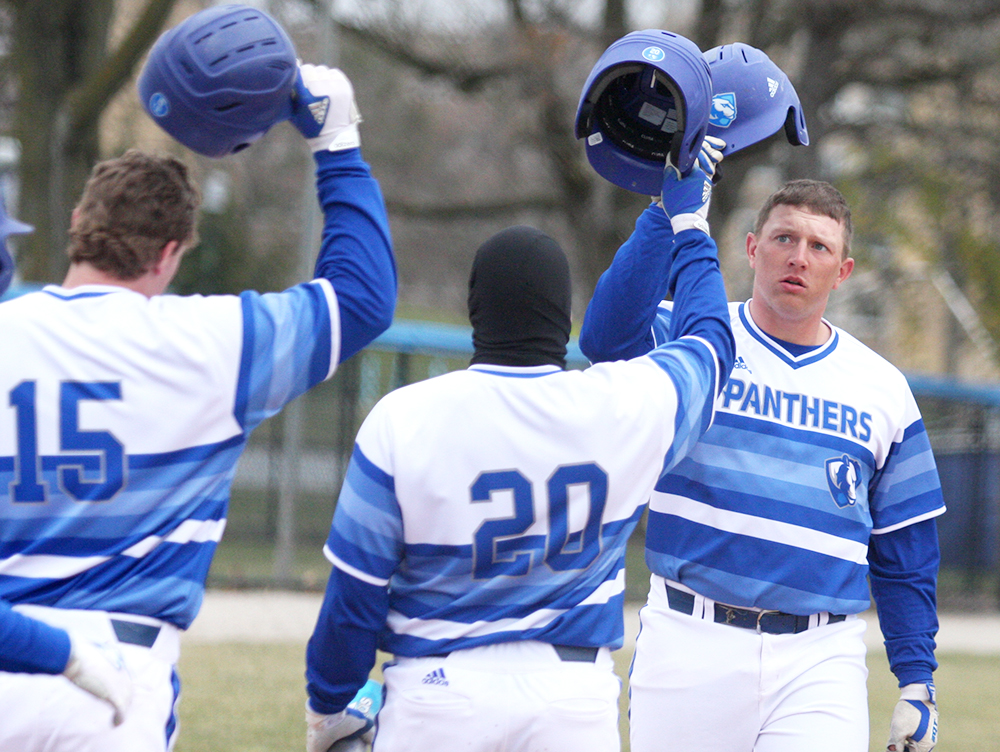 Senior Matt Albert is congragulated at the plate by redshirt junoir Tyler Tesmond (15) and senior Logan Beaman after hitting a three-run home run in the fourth inning in Eastern's 10-8 loss to Indiana State Tuesday at Coaches Stadium. Albert has three home runs this season.