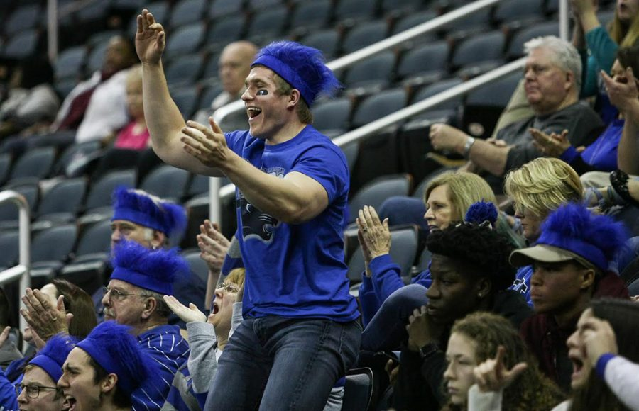 Eastern senior and basketball fan Devin Pierzhalski reacts to a play during the second half of Eastern's opening round game of the OVC tournament. Pierzhalski purchased all of the blue headband wigs for fans traveling on the fan bus Wednesday.