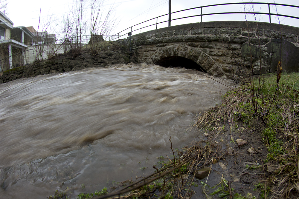 Rushing water pushes through underneath a bridge on Seventh Street Tuesday evening. Severe thunderstorms caused major flooding throughout Charleston and Mattoon on Tuesday.