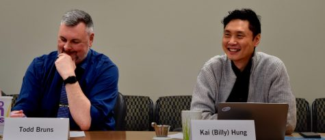 Todd Bruns, the institutional repository librarian, and biological sciences professor Billy Hung at the Faculty Senate meeting on Tuesday in Booth Library. At the meeting Provost Jay Gatrell's reorganization plan was discussed.