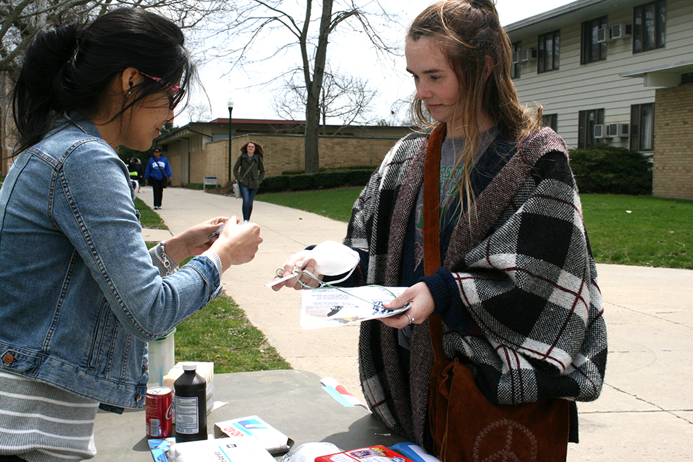 "Olivia Meents, a junior political science major is inspected at the ""health"" station of the refugee camp."