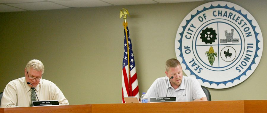 Jeff Lahr, Charleston City Council member, and Brandon Combs, Charleston City Mayor, discuss the agenda at Tuesday nights City Council meeting at City Hall. Combs and the rest of the City Council agreed to grant funding for local businesses to make repairs to their buildings.