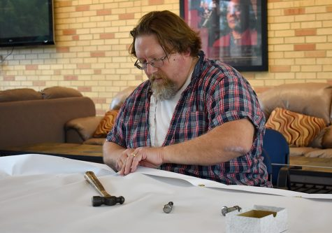 Jon Crask, the Arts & Crafts Coordinator at the Panther Print & Copy Center, works on a banner, Wednesday afternoon in the Bridge Lounge at the Martin Luther King Jr. University Union.