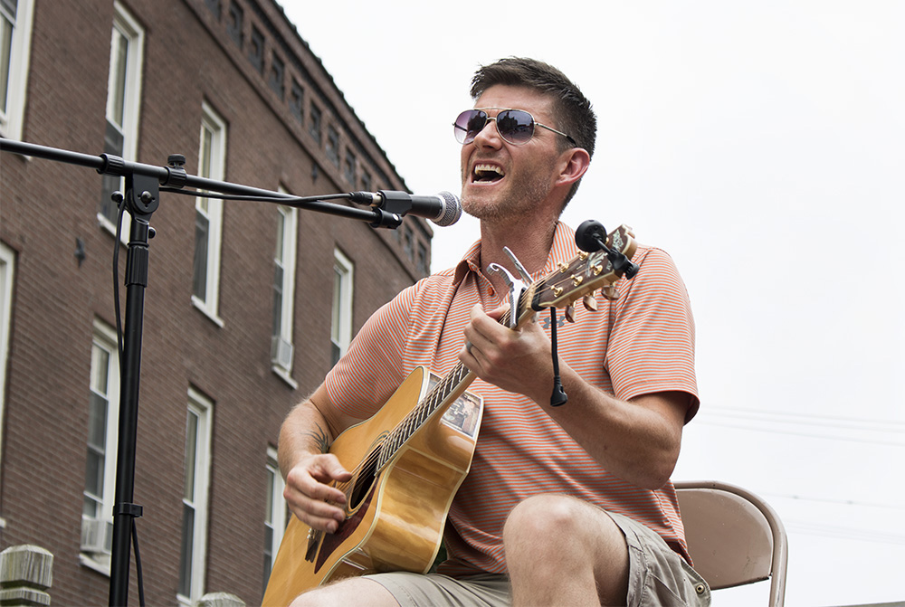 Jake Edwards, performs live music for the crowd at Muse Fest, Saturday evening in the Charleston Square. Edwards told the crowd he was filling in for his sister, who could not make it to the performance.