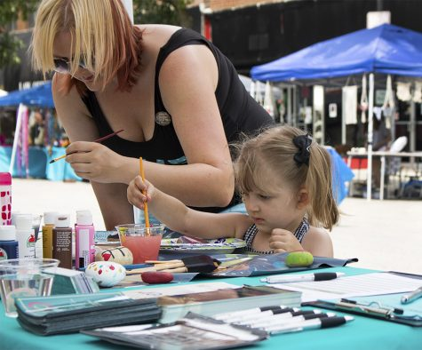 Nikky Davidson, a graduate student in the school of psychology, and her daughter Roxy, paint rocks Saturday morning at Muse Fest in the Charleston Square.
