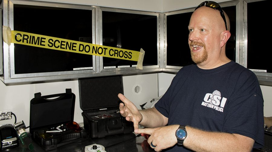 """Police Officer Steve Bridges, describe some of the technology the CSI Unit uses inside """"the lab"""", a trailer CSI Mattoon Police uses to collect and analyze evidence, Wednesday afternoon outside of the Tarble Arts Center."""