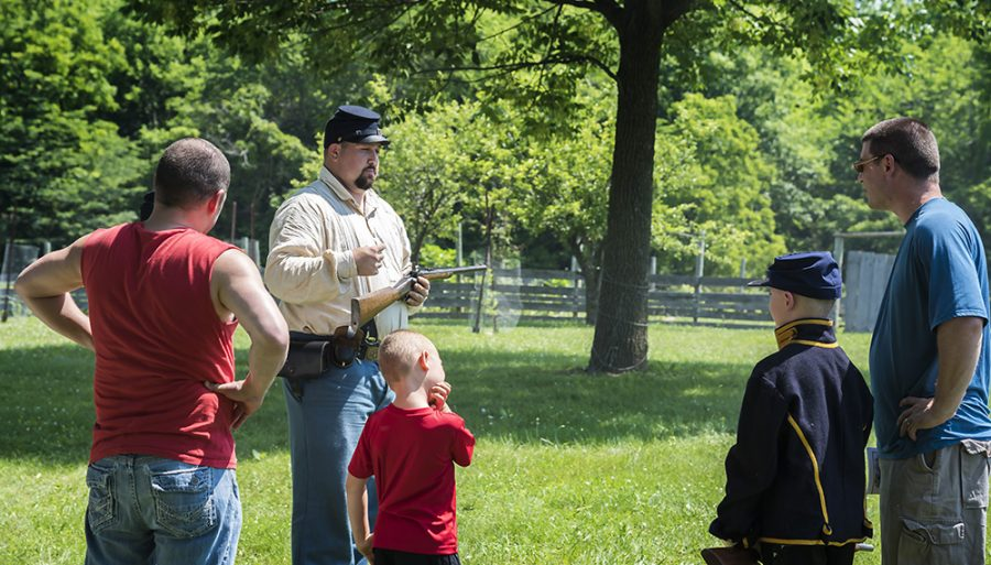 A cavalry member, explains how a Mauser Rifle works to the visitors at Lincoln Log Cabin State Historic Site.