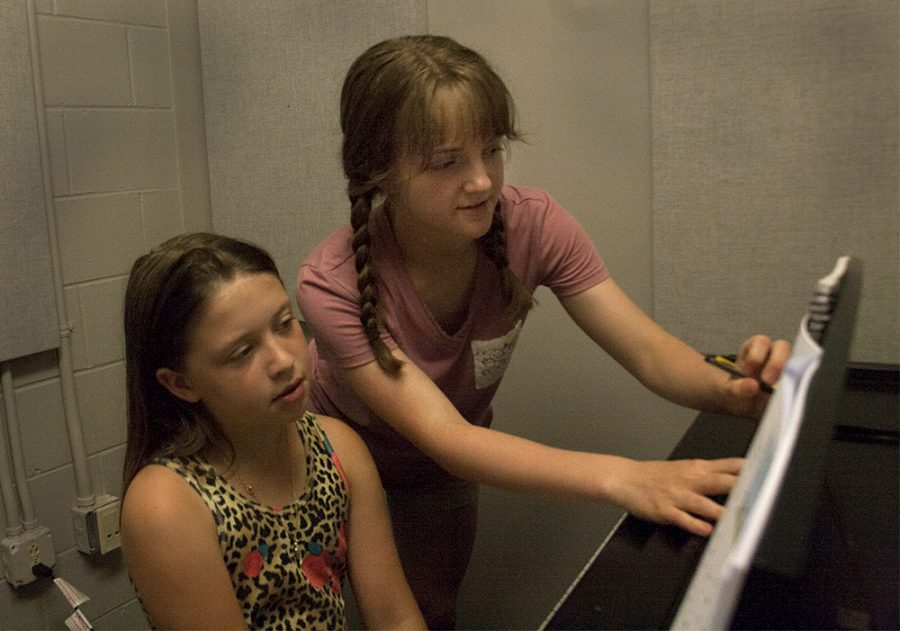 """Abigail Robison, a fourth grader at Jefferson Elementary School, learns to read sheet music from Addison Bayer an Eastern student, Tuesday afternoon in the Doudna Fine Arts Center. """"It's fun and exciting to get lessons because we are about to become family,"""" Robison said. Bayer has been playing for ten years and really enjoys giving lessons, especially during the summer when she has more free time. """"During the school year it's harder to get the time because of classes and practices,"""" Bayer said."""