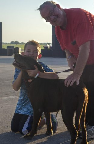 Dave Adamson poses with his grandson Gavin Aprile and Adamson's dog Colby before the Coles County fireworks show Wednesday evening at the Coles County Memorial Airport.