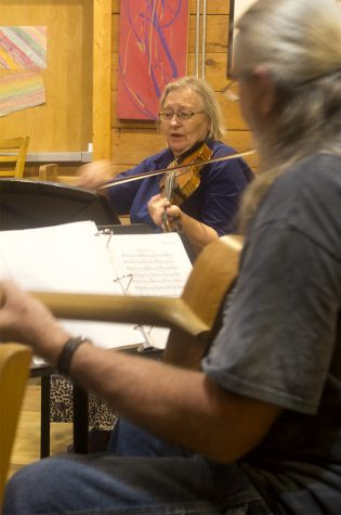 """Gaye Harrison (center), founder and fiddle player for the """"Irish Music Circle,"""" plays a jig at the band's performance Tuesday  evening at Jackson Avenue Coffee."""