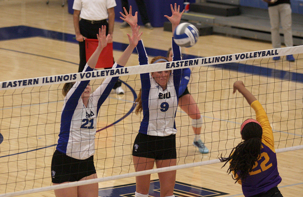 File Photo | The Daily Eastern News Eastern junior Lexi May (21) and graduate Allie Hueston try to block a ball in a match against Western Illinois at Lantz Arena last season. May has 14 spikes already this season.
