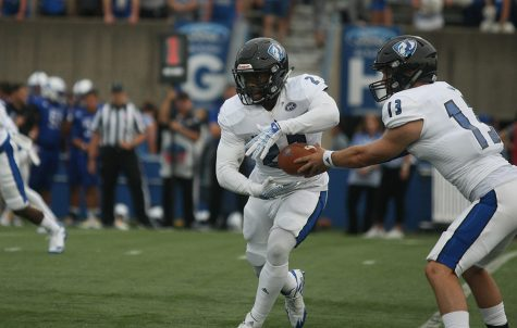 File Photo | The Daily Eastern News Eastern running back Isaiah Johnson takes handoff form Mitch Kimble in a Panthers' 22-20 win over Indiana State last season. Johnson was selected as a preseason all-conference player.