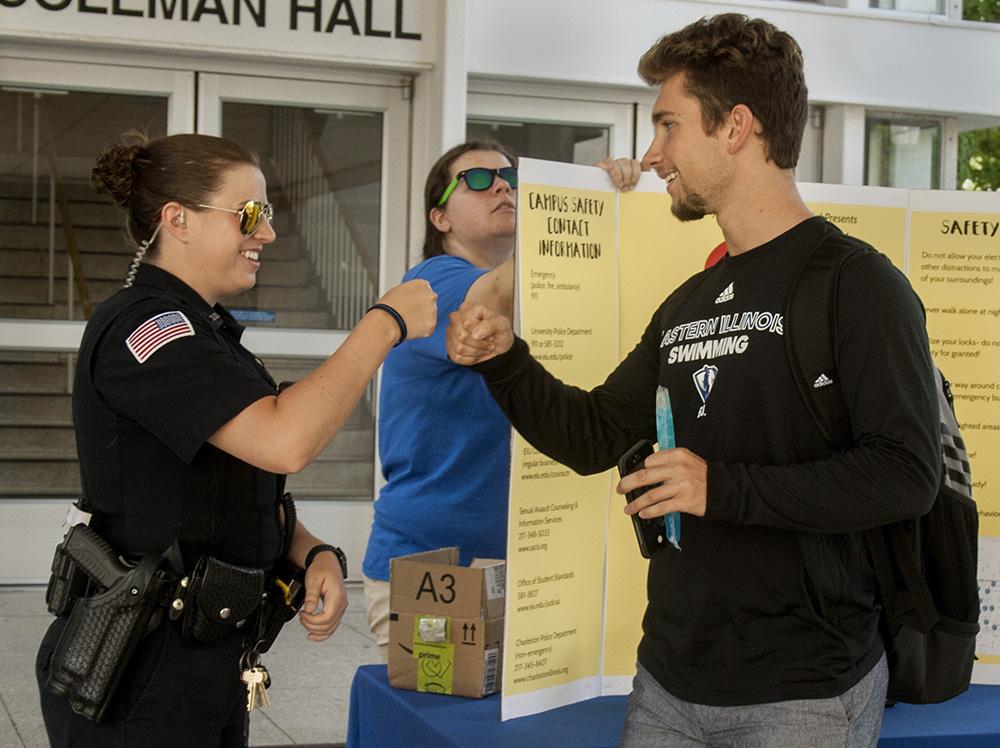 "Ivan Escott (right), a sophomore marketing major, fist bumps Officer Samantha Berry from the University Police Department. ""I love seeing that sort of stuff out here, especially on a college campus,"" Escott said. ""I love seeing support for the police."""