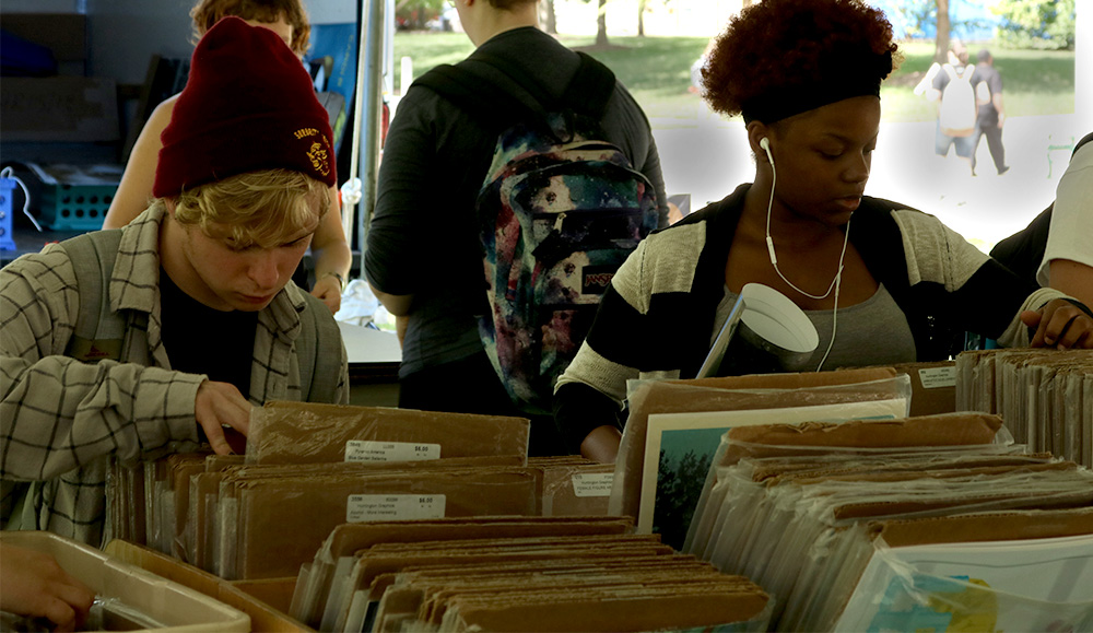Students look through posters at the annual poster sale Tuesday afternoon in the Library Quad. The Department of Art and Design sponsored the event, and the sale is going on until Friday.