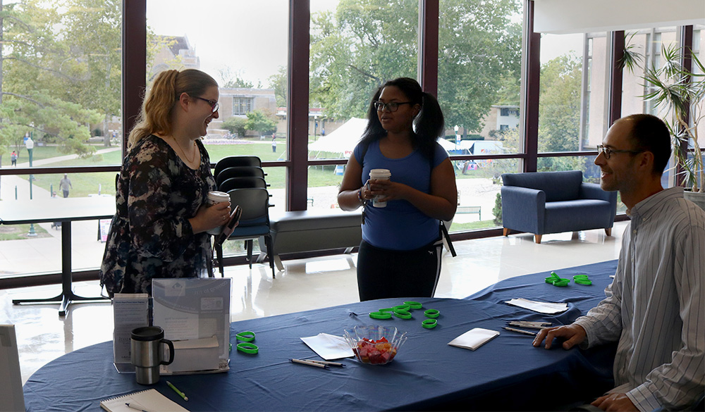 Lauran Vezina, a senior criminology and sociology major, and Tionne Cain a sophomore English major, talk to Micah Miller the program analyst of programs and policies at the Illinois Secretary of State Tuesday afternoon in the bridge lounge at the Martin Luther King Jr. University Union.