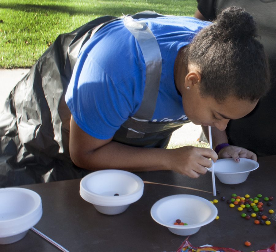 Shakria Williams, a freshman majoring in special education who was a part of Lawson Hall, uses a straw to get Skittles into a bowl at the ROCFest obstacle course Tuesday.