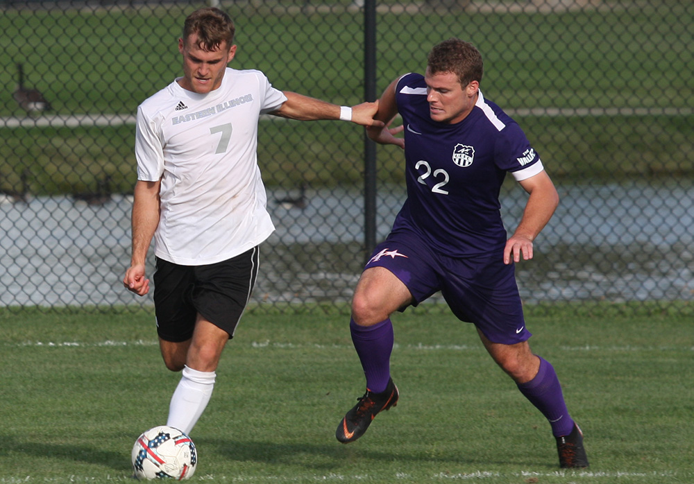 Eastern senior midfielder Jake Andrews holds off an Evasnville defender as he gets ready to cross the ball into the box. Eastern drew 1-1 with Evansville at Lakeside Field on Aug. 31.
