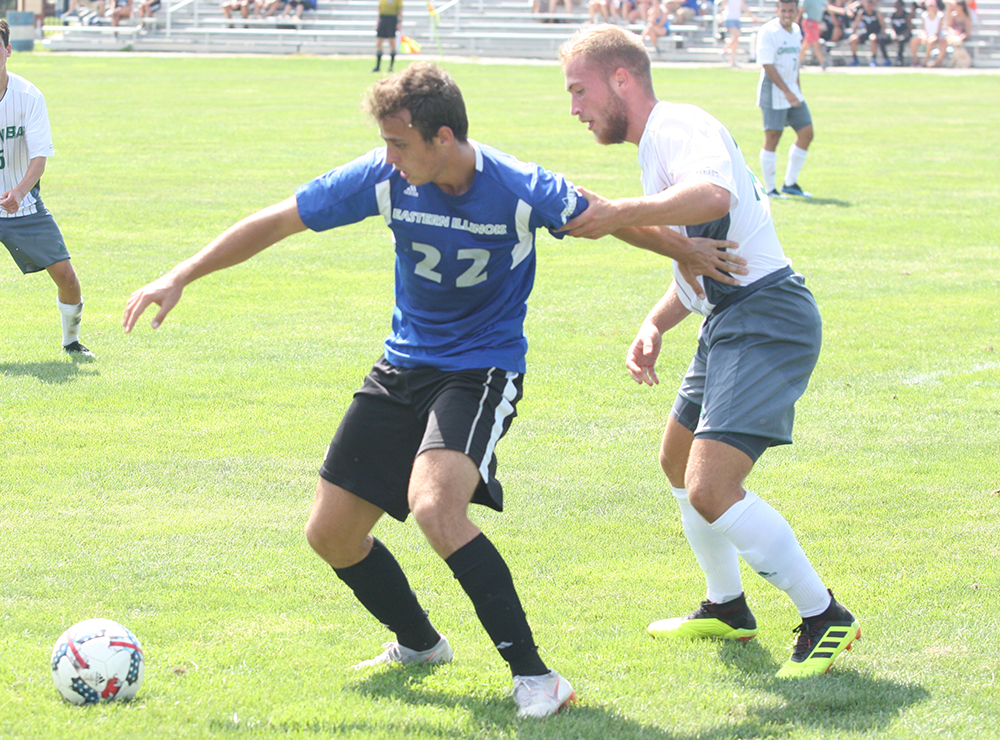 Redshirt-freshman forward Luke Kurili holds off a Green Bay defender during Eastern's 1-0 loss at Lakeside Field on Sept. 2.