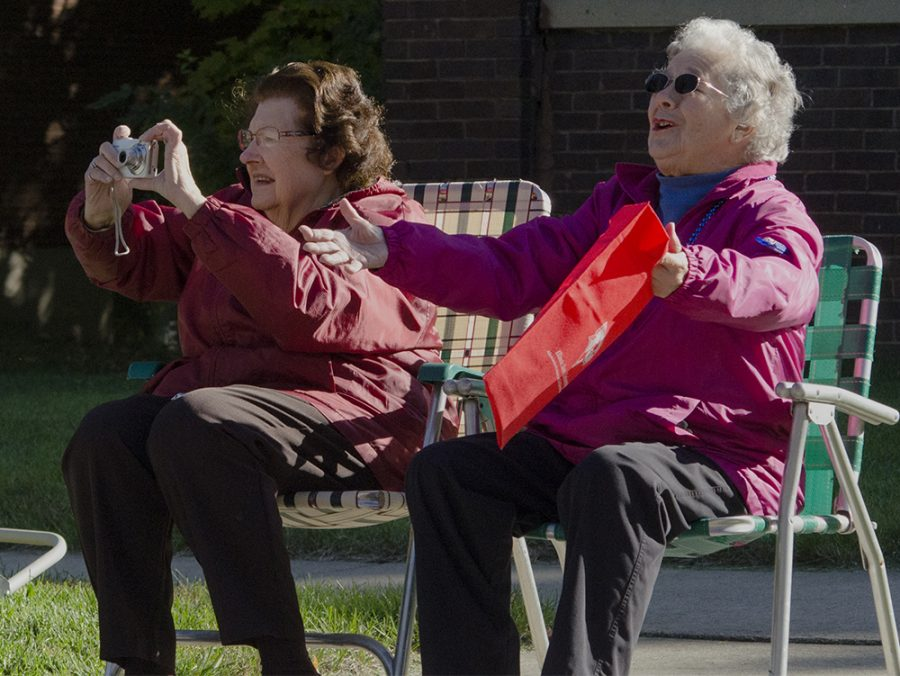 Charleston resident Jeanette Baer (left) takes a picture of her daughter Lynette Drake, the interim vice president of student affairs, while her best friend Joan Gregg (right) stretches out her arms to ask for candy during the 2018 Homecoming Parade on Saturday. The two friends were sitting in front of Baer's house and said the best part of the parade was seeing everyone they knew and, of course, the candy.