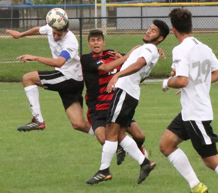 Two Eastern players collide with a Northern Illinois defender as all three of them leap in the air to head a ball. Eastern lost the game 2-0 which was played at Lakeside Field on Sept. 21 at Lakeside Field.