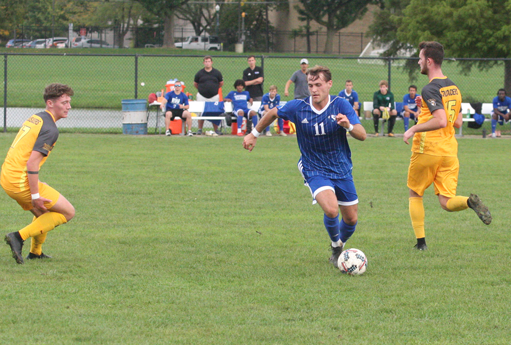Toby Andrews dribbles the ball between a pair of Valparaiso defenders during the men's soccer team's 2-1 loss at Lakeside Field on Oct. 10.
