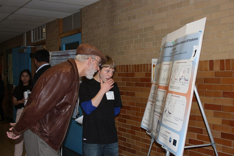 Derric Meyer (center), explains his research project to a guest Thursday afternoon at the 17th Student Research Celebration at the Physical Science Building.