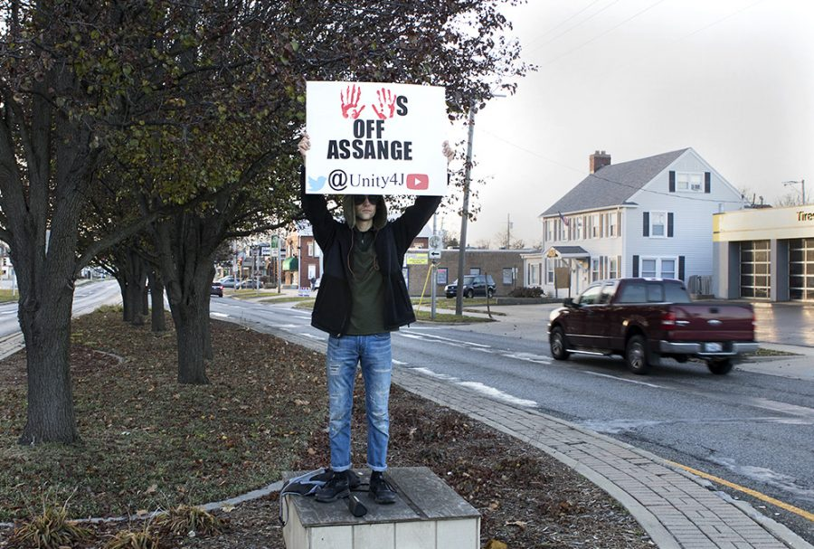 """Clayton Redden, a Charleston resident, protests the Julian Assange case Saturday afternoon on Lincoln Ave. outside of Old Main. """"I'm trying to bring Republicans and Democrats together, to spread awareness about the persecution and death of independent journalism."""" Redden said. """"Spread awareness about the slow crucifixion of Julian Assange who has been exposing war crimes."""""""