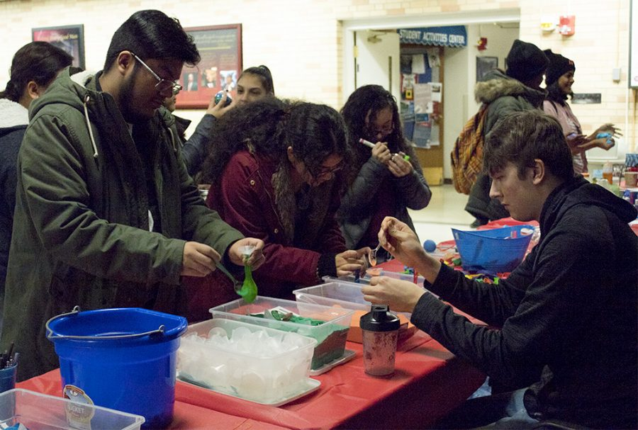 "Kyara Morales, a freshman English major, and Luis Paniagua, a freshman art major, make stress balls out of balloons and sand at the event Thursday evening. ""I've never made any of this before,"" Morales said. ""I wanted to try it out,"""