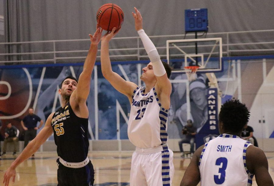 Ben Harvey attempts a jump shot with a Fort Wayne defender lunging toward him to block it during Eastern's 104-60 loss Wednesday in Lantz Arena.