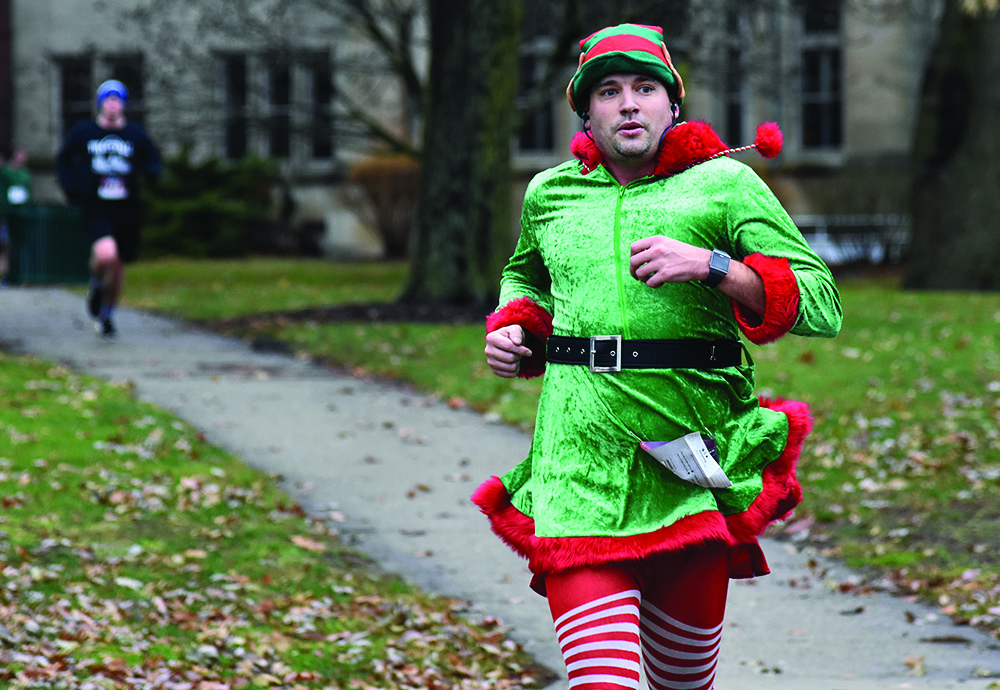 Kaj Holm, a teacher at Charleston High School, wore a Christmas-themed outfit for Saturday's Holiday Hustle 5K run/walk. He was the fourth person to cross the finish line in front of Old Main with a time of 21 minutes and 55 seconds.