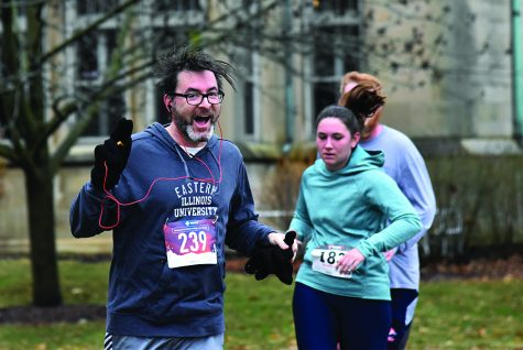 English professor C.C. Wharram hold a thumb while running toward the finish line during the Holiday Hustle 5K run/walk Saturday in front of Old Main.