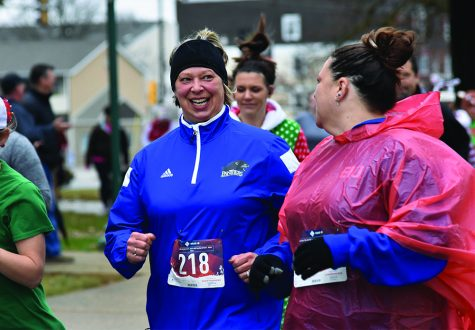 Two participants talk while walking in the Holiday Hustle 5K run/walk Saturday at Old Main.