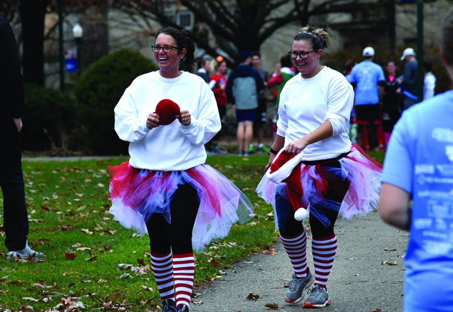 Two women dressed up in Christmas-themed outfits walked to the finish line during the Holiday Hustle 5K run/walk.
