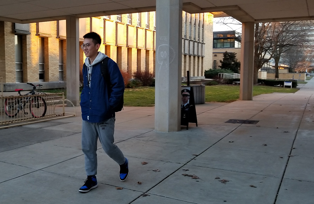 """George Gao, a junior biological science major, takes a walk around campus Tuesday afternoon. He said he was enjoying the nice weather as he says, """"It isn't bad for January. It was really nice today."""""""