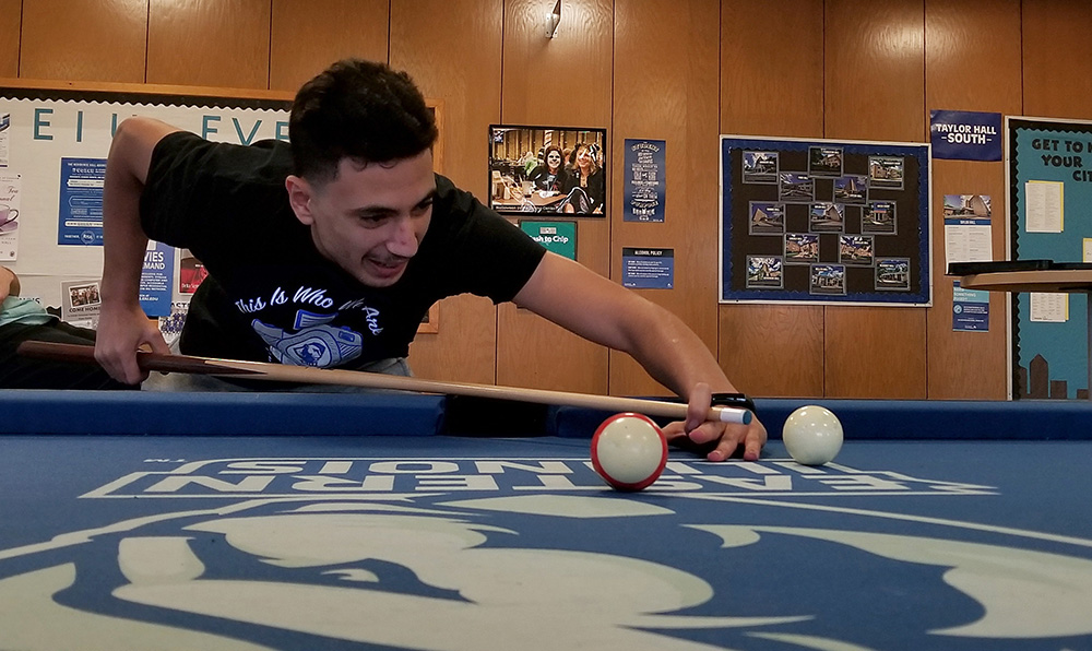 Saad Elkhelfi, a freshman marketing major, enjoys a close game of pool with his friends Tuesday afternoon in the Taylor Hall lobby.