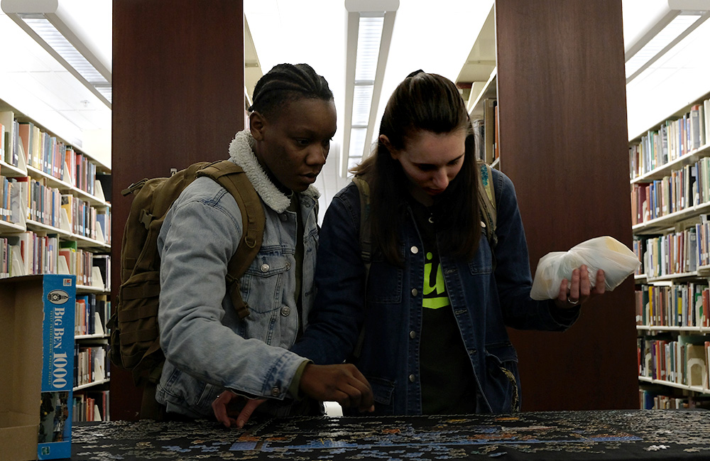 Chermaine King, a sophomore construction management major, and Sarah Gonpers, a sophomore pre-physical therapy major, add pieces to a puzzle Thursday night in Booth Library. It was a puzzle of a dock with boats and fishing nets.