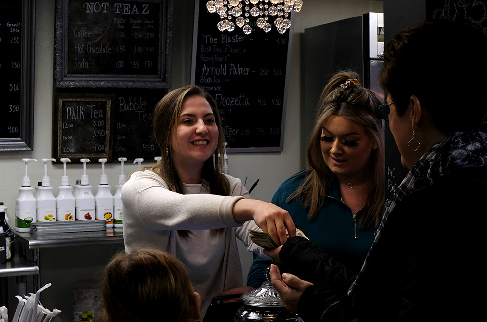 Mikayla Kuznicki, a senior at Charleston High School, and Hali Cordes, a Lake Land College student studying aesthetics, talk to a customer while Kuznicki gives back her change Monday afternoon at SweeTea'z on Lincoln Ave.