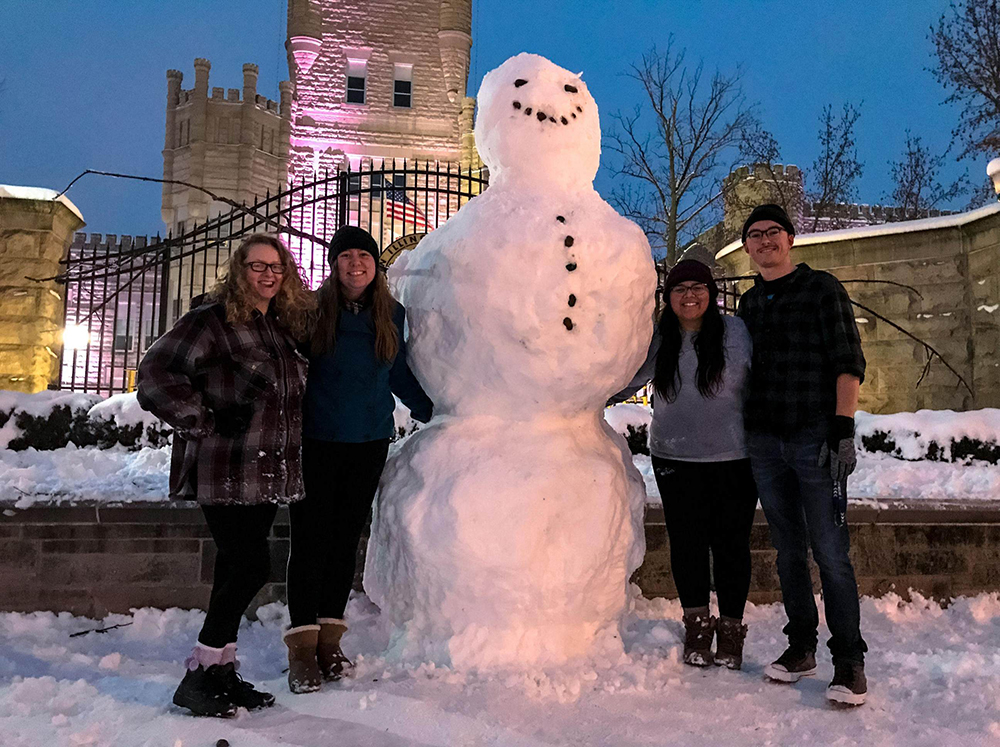 (From left to right) Sophomores Lucy Hill, a music performance major, Resa Fuller, a music performance major, Jessica Stewart, an English education major, and Lucas Lower, a computer science major stand next to a snowman they built Saturday night in front of Old Main. The snowman was knocked down Saturday night.